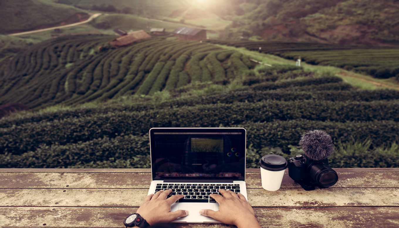 Top view creator or editor working use on laptop outdoor in green tea fields this is lifestyle of vlogger